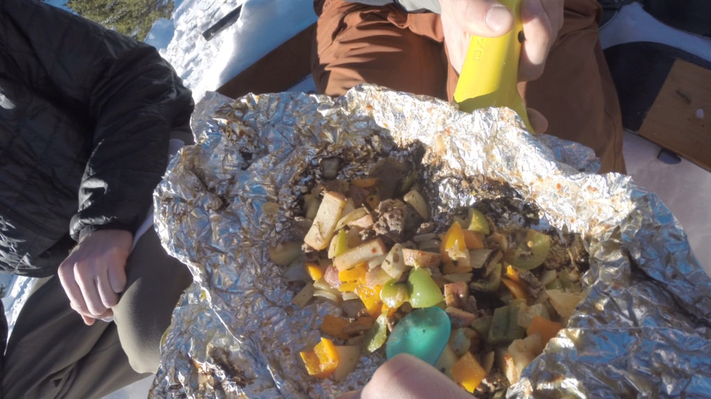 Digging into a campfire foil packs meal