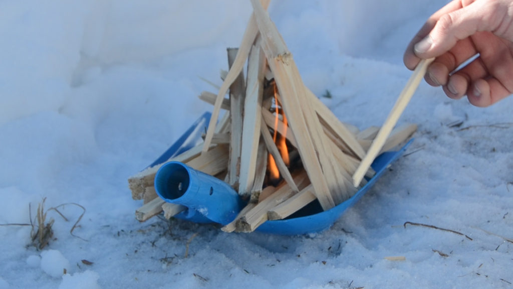 Use a snow shovel to start a fire in the snow